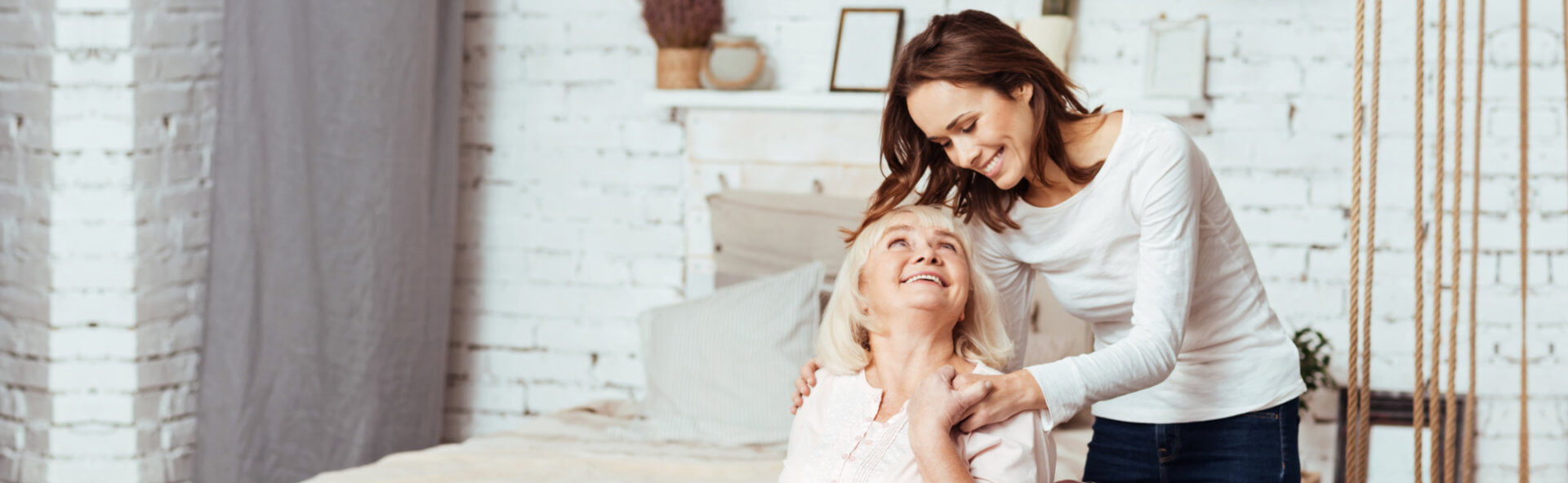 senior and a caregiver smiling each other