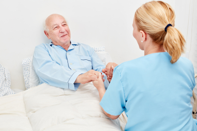 caregiver and senior holding hands while smiling
