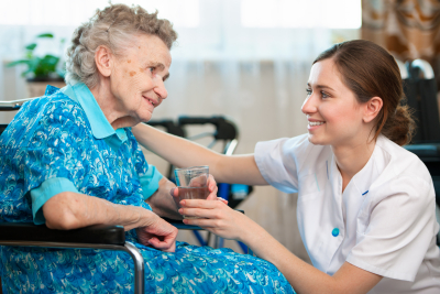 caregiver giving a glass of water to senior woman